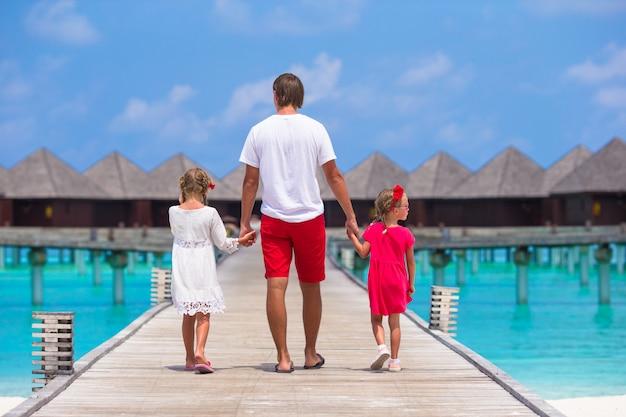 Meisjes met papa op houten pier dichtbij waterbungalow bij exotische toevlucht