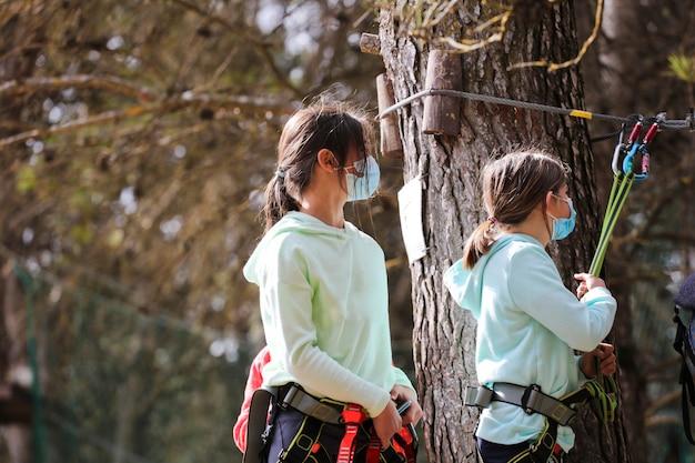 Meisjes met sportkleding en coronavirusbeschermingsmasker springen van boom naar boomluifel installatiebos op de achtergrond