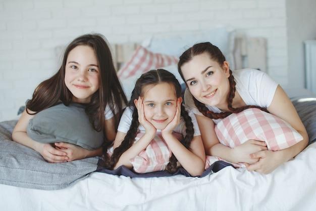 Meisjes met staartjes en een jongere broer, een gezin in witte t-shirts en jeans spelen met kussens op het bed. het concept van een gelukkig gezin.
