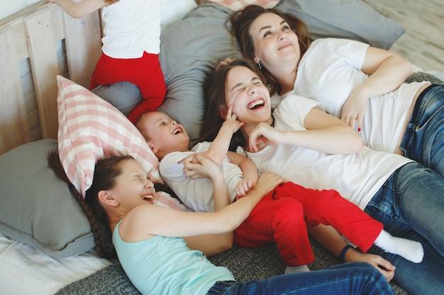 Meisjes met staartjes en een jongere broer, een gezin in witte t-shirts en spijkerbroeken liggen op de grond met kussens, glimlachen en lachen. het concept van een gelukkig gezin.