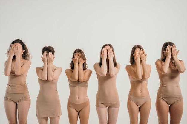 Meisjes met verschillende figuren in beige ondergoed de meisjes bedekken hun gezicht met hun handen een plek...