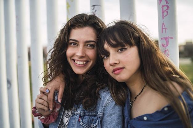 Meisjes naast elkaar achter een wit metalen hek