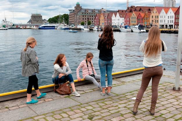 Meisjes nemen foto van een stad, bryggen, bergen, noorwegen