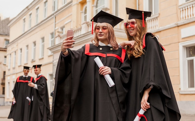 Meisjes nemen selfie bij afstuderen