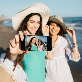 Meisjes nemen selfie op het strand