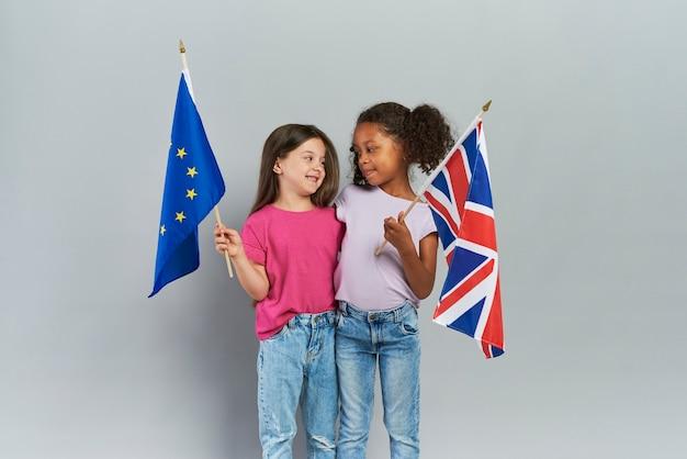 Meisjes omarmen en houden de vlaggen van de britse en europese unie vast