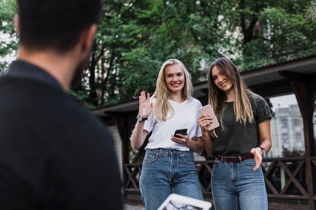 Meisjes ontmoeten een vriend en zeggen hallo