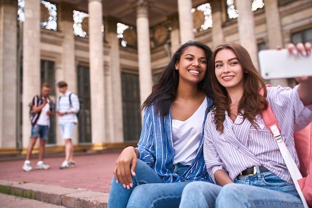 Meisjes ontspannen in de pauze en nemen selfies terwijl ze op straat zitten
