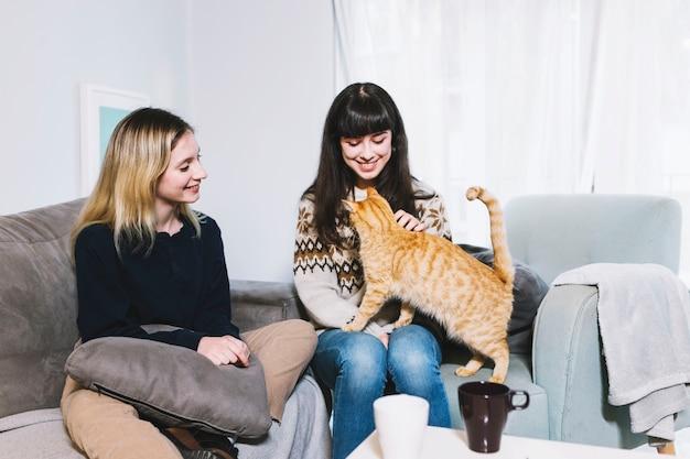 Meisjes op bank met plezier met kat