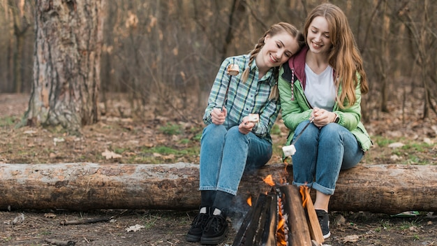 Meisjes opwarmen bij vreugdevuur