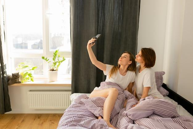 Meisjes paar doen selfie in het bed lachen en plezier maken in valentijnsdag