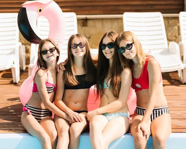 Meisjes poseren bij zwembad