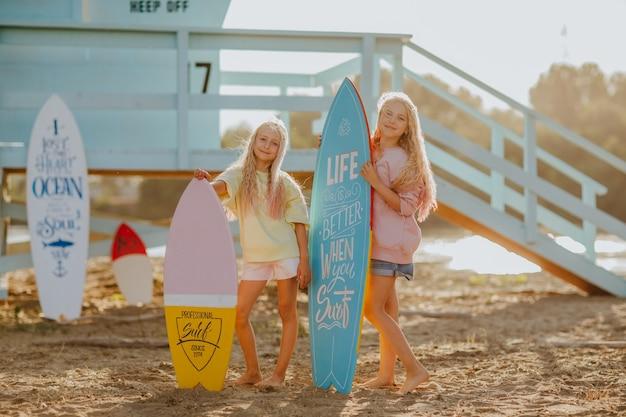 Meisjes poseren met surfplanken tegen blauwe badmeestertoren op het zandstrand