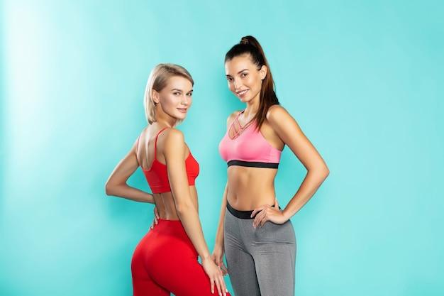 Meisjes power twee jonge en aantrekkelijke sportieve meisjes in sportkleding camera kijken en glimlachen terwijl