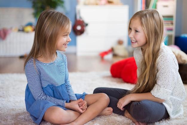 Meisjes praten met elkaar in de woonkamer