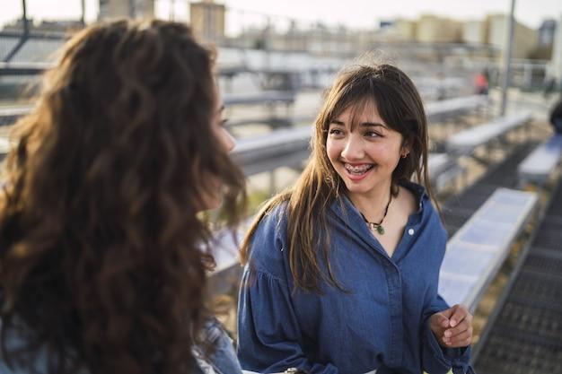 Meisjes praten naast elkaar achter gebouwen