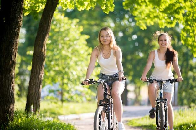 Meisjes rijden fiets en lachend