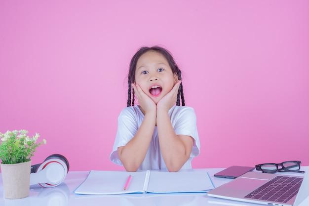 Meisjes schrijven boeken op een roze achtergrond.