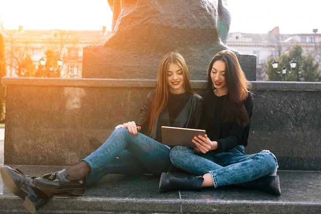 Meisjes siiting in de vloer op zoek naar een tablet
