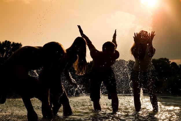 Meisjes silhouetten spelen in het water tegen de zon