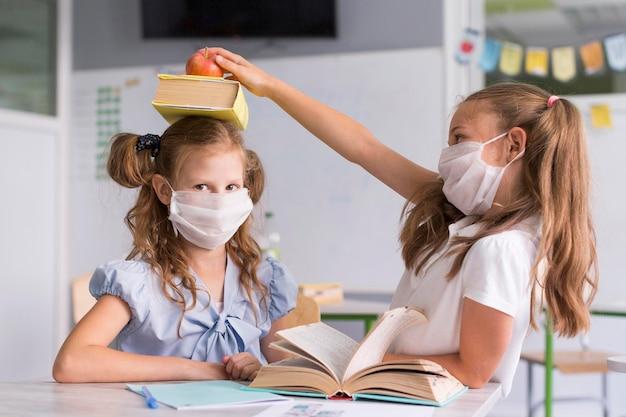 Meisjes spelen in de klas terwijl ze medische maskers dragen