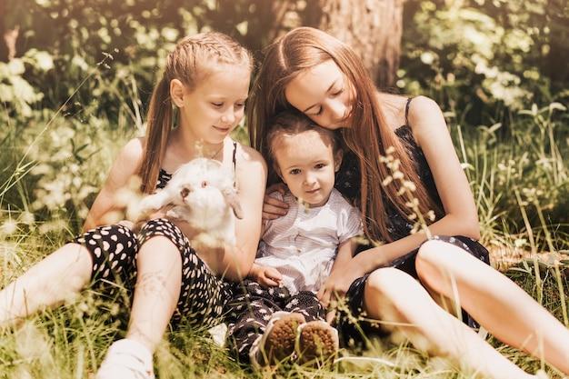 Meisjes spelen in het park met een wit konijn in het park. lente leuke activiteit voor kinderen. pasen