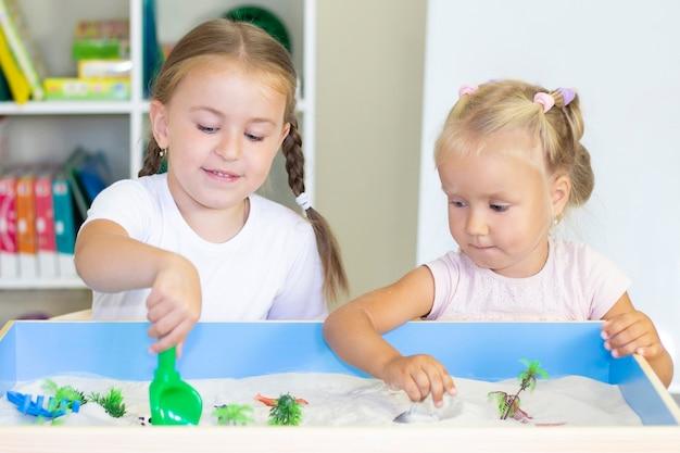 Meisjes spelen in het zand, educatieve activiteit