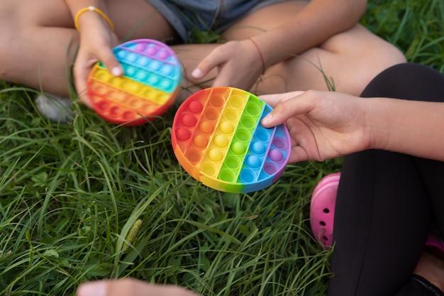 Meisjes spelen kleurrijke pop-it pop-it speelgoed buiten op groen gras