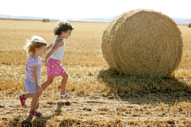 Meisjes spelen met de ronde tarwe gedroogde balen