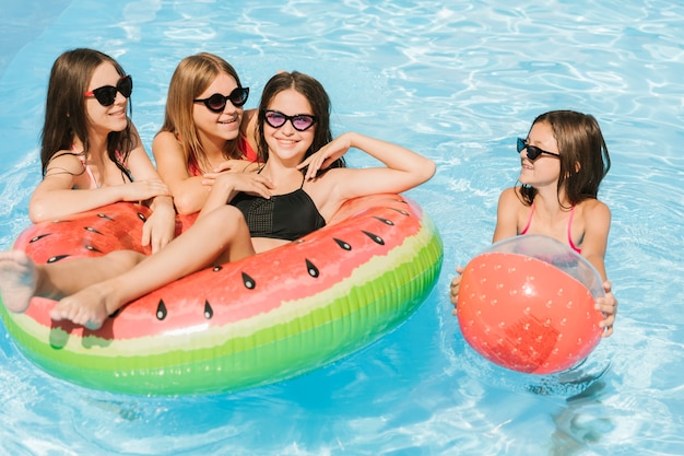 Meisjes spelen met strandbal en floatie