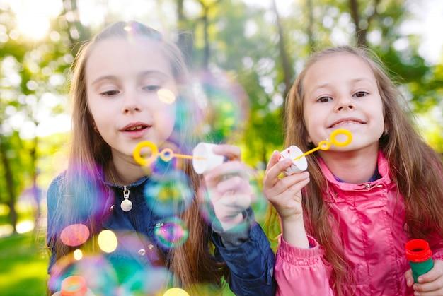 Meisjes spelen met zeepbellen.