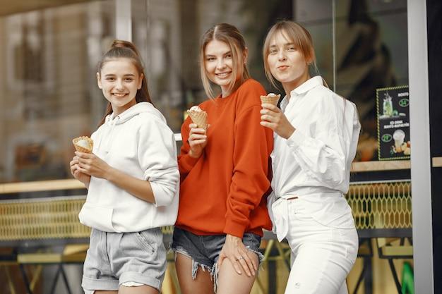 Meisjes staan in een zomerstad met ijs