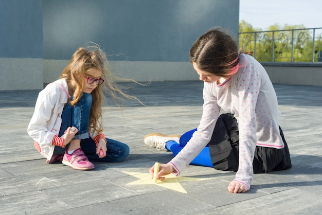 Meisjes tekenen op het asfalt gekleurde krijtjes symbool