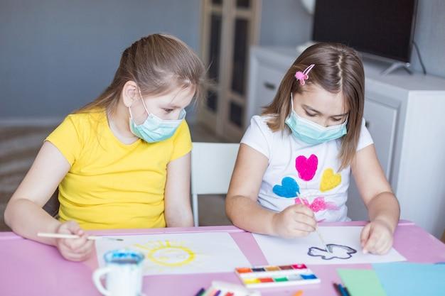 Meisjes thuis tekenen tijdens quarantaine in steriele maskers. jeugdspelen, tekenkunsten, thuis blijven concept
