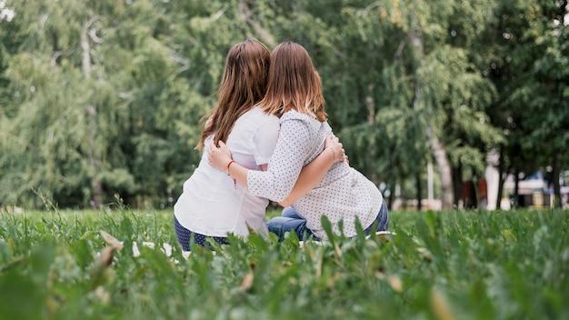Meisjes van achteren omhelzen elkaar