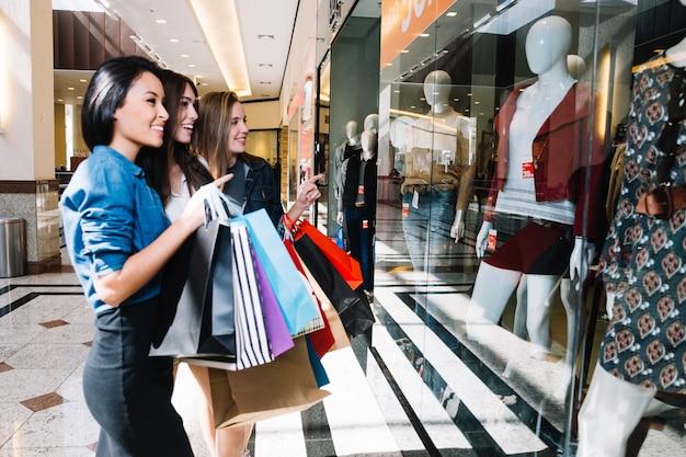 Meisjes verkennen winkelvenster met opwinding