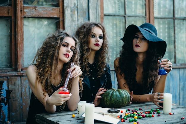 Meisjes vermomd als heksen zitten aan een tafel met een pompoen en een rode drankje en andere blue