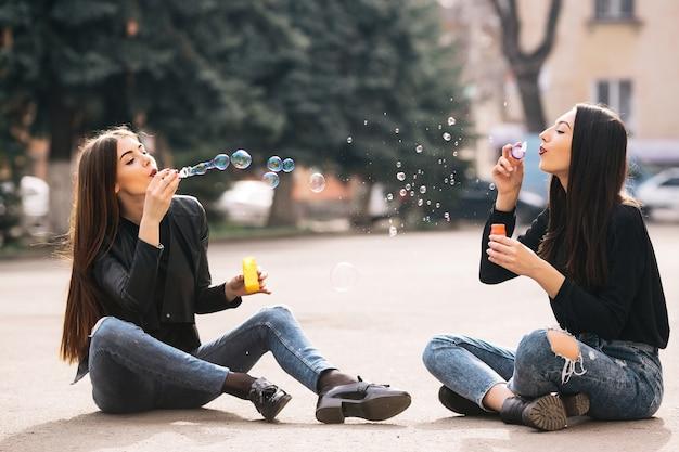 Meisjes vooraan blowing bubbles