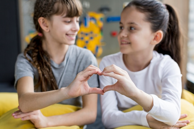 Meisjes vormen hart met handen