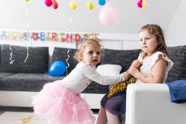 Meisjes worstelen om klatergoud op feestje