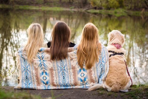 Meisjes zitten aan de oevers van de rivier