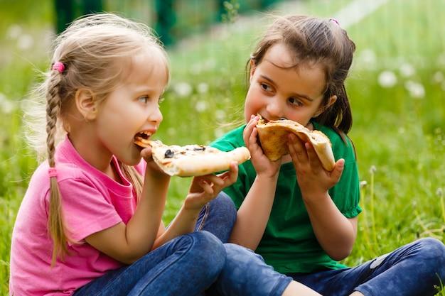 Meisjes zitten en pizza eten