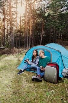 Meisjes zitten in de tent bij zonsondergang