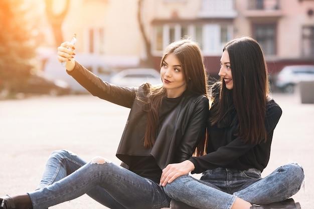 Meisjes zitten in de vloer tijdens het nemen van een selfie