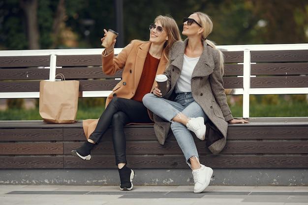 Meisjes zitten in een lentestad en houden koffie in haar hand