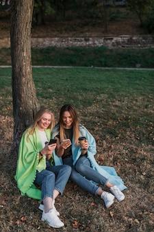 Meisjes zitten in park naast een boom