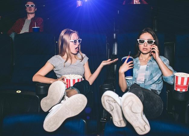 Meisjes zitten in stoelen in bioscoopzaal. brunette is aan het telefoneren terwijl haar vriendin haar een opmerking maakt. meisje links is boos en geïrriteerd.