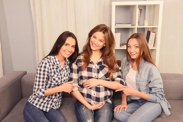 Meisjes zitten op de bank en raken de buik van hun zwangere vriendin aan