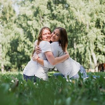 Meisjes zitten op gras en knuffelen