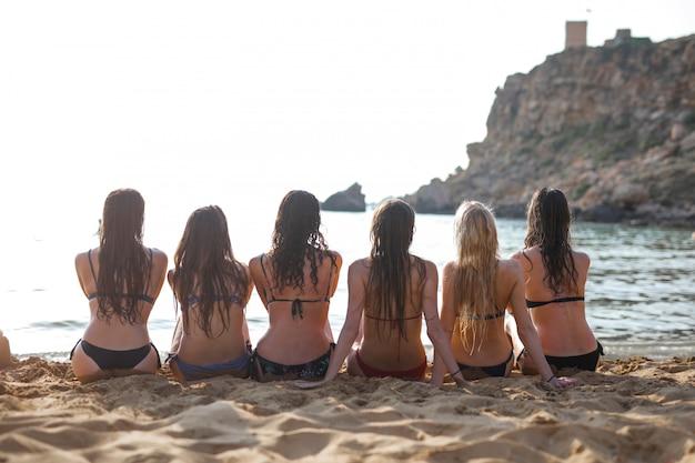 Meisjes zitten op het strand